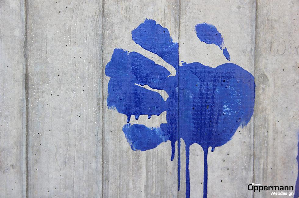 Die blaue Hand an der grauen Wand